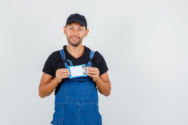 Jeune chargeur en uniforme tenant un mini presse-papiers et souriant, vue de face.