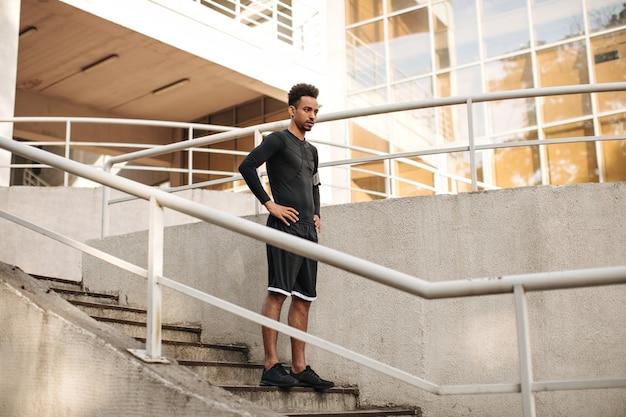Jeune charmant homme brune à la peau foncée en short et t-shirt noir à manches longues descendant les escaliers à l'extérieur