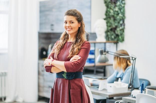 Jeune charmante femme souriante propriétaire de salon de beauté nail bar, concept de propre petite entreprise