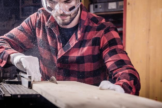 Un jeune charpentier au travail avec une planche de bois dans une menuiserie