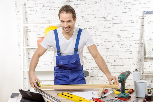 Jeune charpentier mesurant une planche de bois