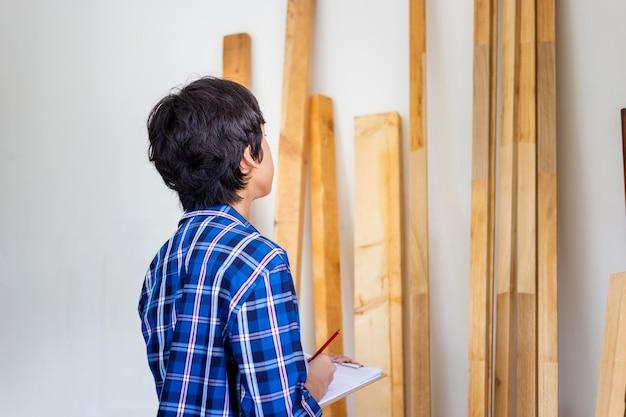 Jeune charpentier vérifiant le stock de boiseries au stockage d'usine. homme comptant l'inventaire du bois de poutres en bois dans l'atelier de menuiserie