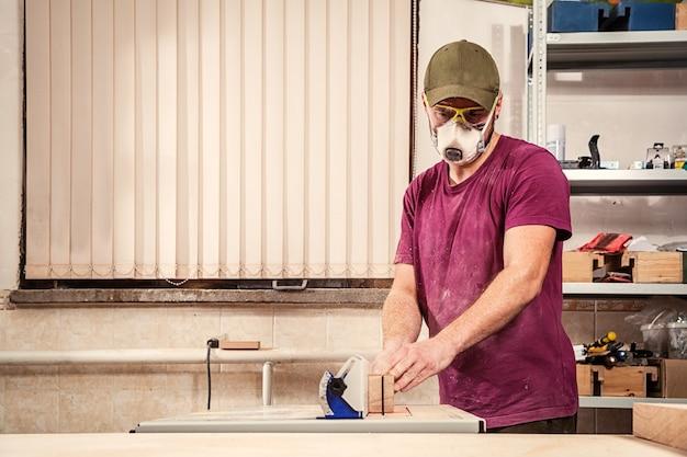 Un jeune charpentier vêtu d'une chemise violette, d'une casquette verte et d'un masque de protection scie une planche de bois avec une scie circulaire sur la table de l'atelier, de la sciure de bois s'est envolée sur les côtés