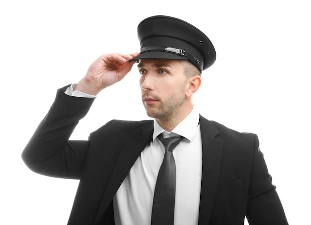 Jeune chauffeur ajustant son chapeau sur fond blanc