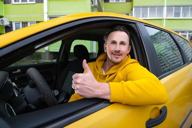 Le jeune chauffeur de taxi masculin heureux s'assied derrière la roue d'un taxi et montre comme