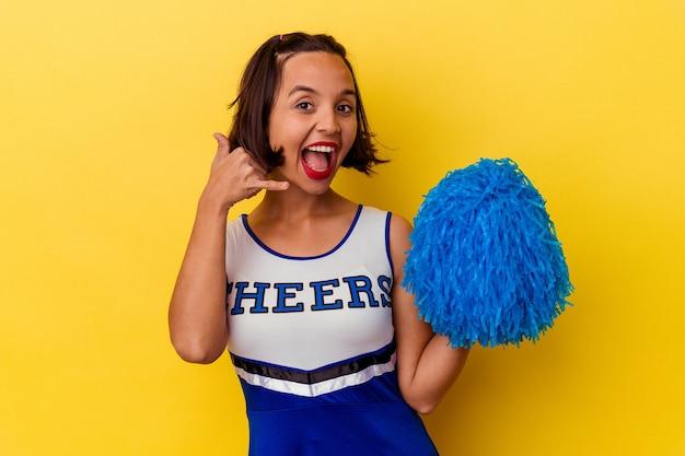 Jeune cheerleader métisse femme isolée sur mur jaune montrant un geste d'appel de téléphone mobile avec les doigts