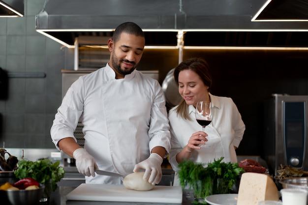 Jeune chef africain cuisine avec sa petite amie caucasienne dans la cuisine