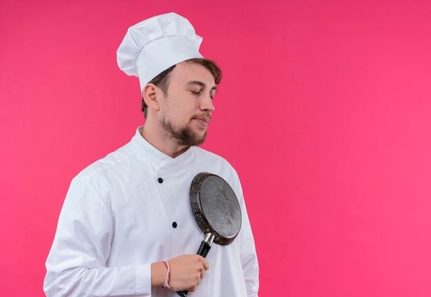 Un jeune chef barbu calme homme en uniforme blanc tenant une poêle à frire avec les yeux fermés sur un mur rose