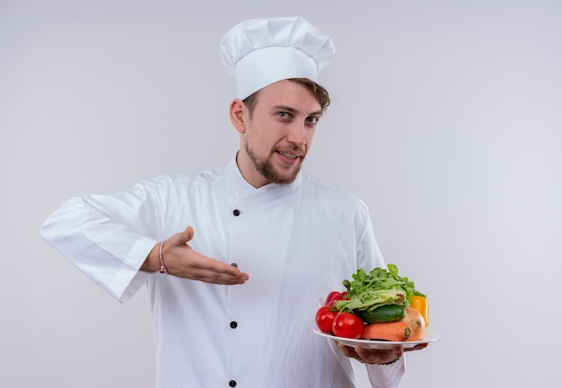 Un jeune chef barbu content homme vêtu d'un uniforme de cuisinière blanc et chapeau tenant une assiette blanche avec des légumes frais tels que tomates, concombres, laitue sur un mur blanc