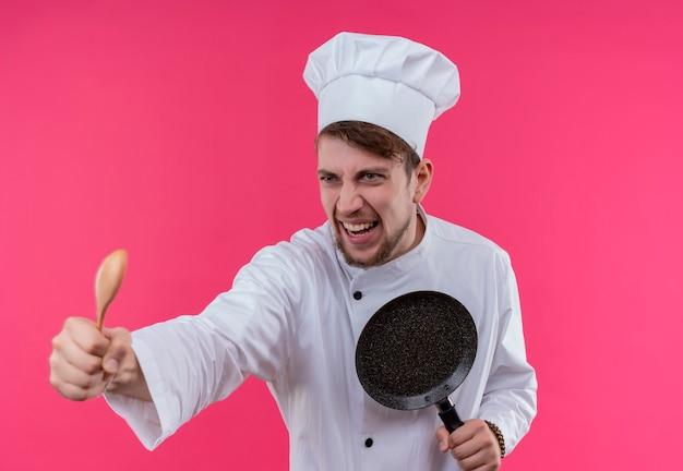 Un jeune chef barbu furieux homme en uniforme blanc attaquant avec cuillère en bois et poêle à frire en se tenant debout sur un mur rose