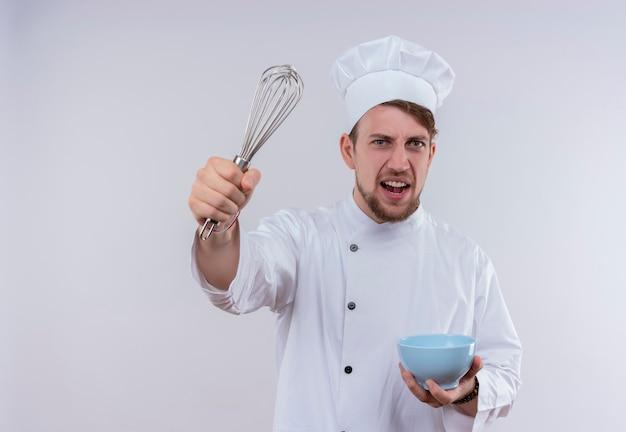 Un jeune chef barbu furieux homme vêtu de l'uniforme de cuisinière blanche et d'un chapeau soulevant une cuillère mélangeuse avec bol bleu dans l'autre main tout en regardant sur un mur blanc