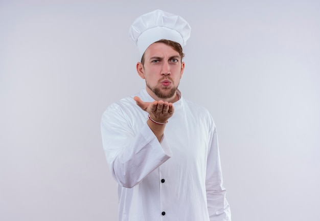 Un jeune chef barbu homme portant l'uniforme de cuisinière blanc et un chapeau envoyant un baiser en se tenant debout et à la recherche sur un mur blanc