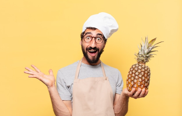 Jeune chef barbu homme surpris expression tenant un ananas