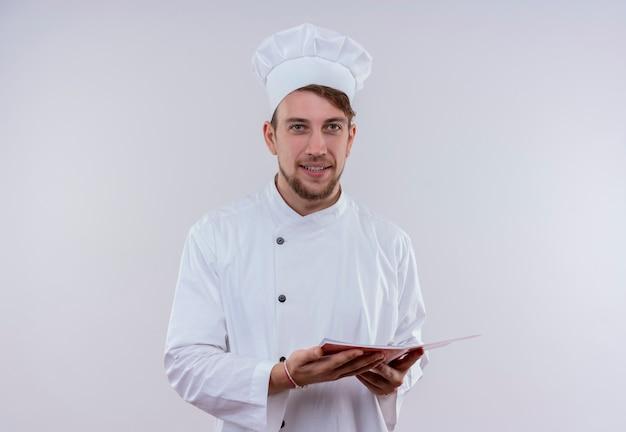 Un jeune chef barbu souriant homme vêtu d'un uniforme de cuisinière blanc et hat holding notebook tout en regardant sur un mur blanc