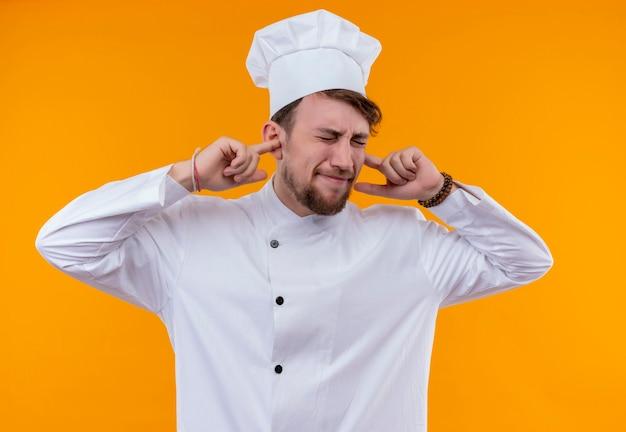 Un jeune chef barbu stressant homme en uniforme blanc tenant les oreilles avec l'index avec les yeux fermés sur un mur orange