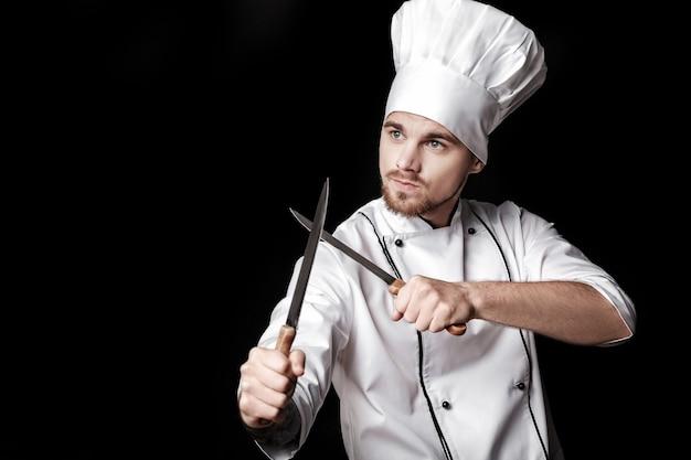 Jeune chef barbu en uniforme blanc tient deux couteaux sur fond noir