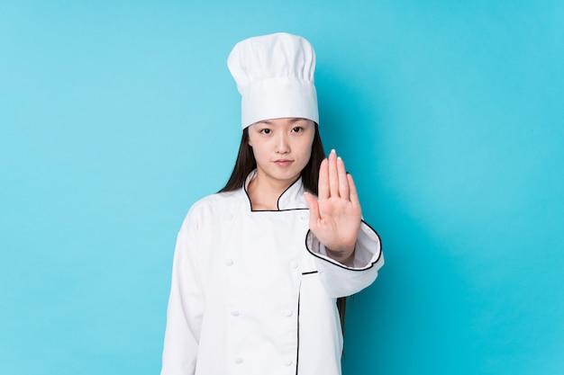 Jeune chef chinois femme isolée debout avec la main tendue montrant le panneau d'arrêt, vous empêchant.
