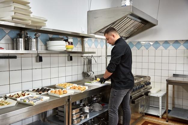 Jeune chef cuisinier en tunique noire prépare des collations de restauration