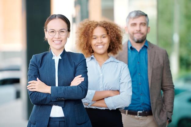 Jeune chef d'entreprise gai en tenue de soirée et son équipe derrière vous regardant avec le sourire en se tenant debout dans la rangée