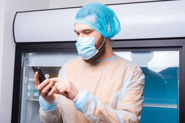 Jeune chef homme dans la cuisine à l'aide de smartphone pendant covid-19
