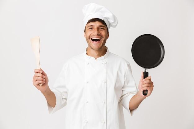Jeune chef homme debout isolé sur mur blanc tenant la vaisselle.