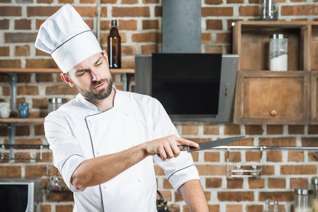 Jeune chef masculin en regardant couteau aiguisé