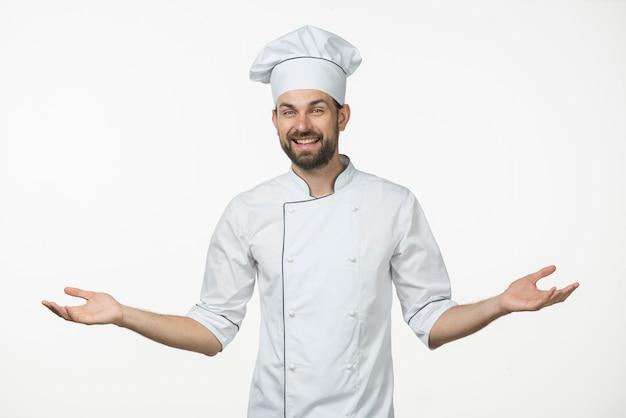 Jeune chef masculin en uniforme debout sur fond blanc, haussant les épaules