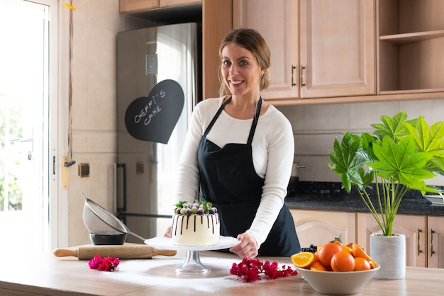 Jeune chef pâtissier cuisine un délicieux gâteau au chocolat blanc fait maison avec des fruits dans la cuisine
