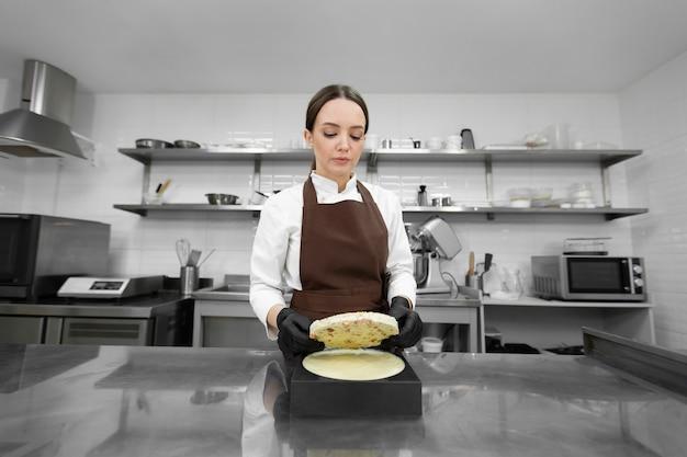 Le jeune chef pâtissier met une génoise aux noix dans un gâteau mousse