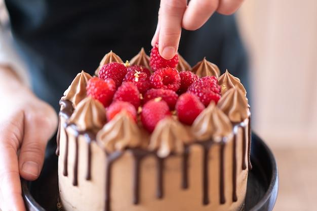 Jeune chef pâtissier préparant un délicieux gâteau au chocolat fait maison avec des fruits dans la cuisine