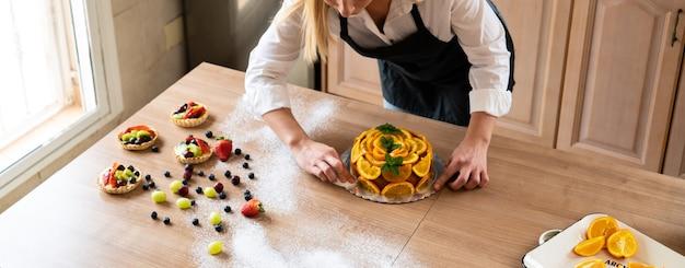 Jeune chef pâtissier préparant un gâteau à l'orange avec des tranches d'oranges