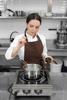 Une jeune chef pâtissière ajoute de la pâte de pistache au sirop bouillant