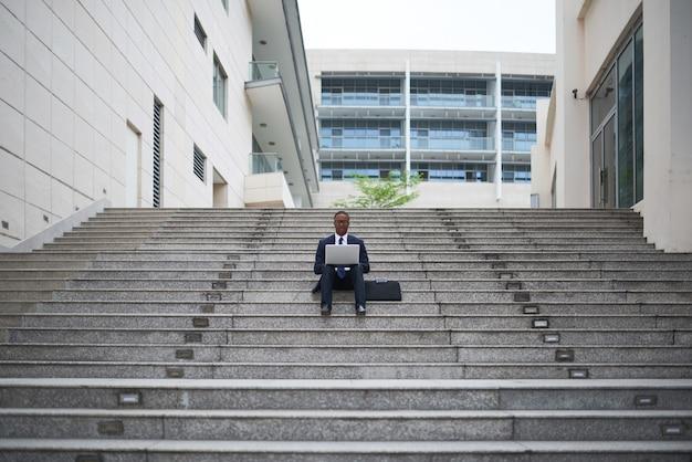 Jeune chef de projet d'une entreprise informatique assis à l'extérieur et travaillant sur des documents et des contrats avant de rencontrer des collègues
