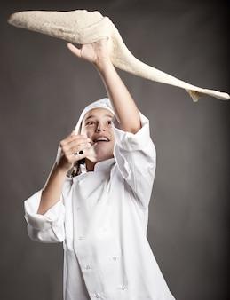 Jeune chef travaillant la pâte à pizza