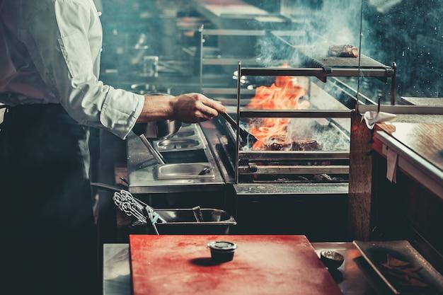 Jeune chef en uniforme blanc cuisson de la viande