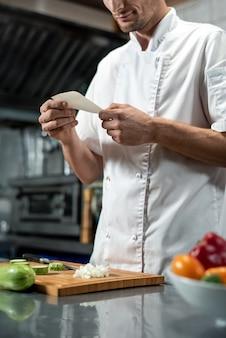 Jeune chef en uniforme regardant la liste des ingrédients pour la salade de légumes tout en tenant du papier sur de l'oignon haché sur une planche de bois