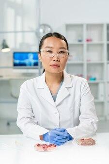 Jeune chercheuse asiatique gantée en blouse blanche et lunettes assise sur le lieu de travail avec deux échantillons de viande de légumes crus dans des boîtes de pétri