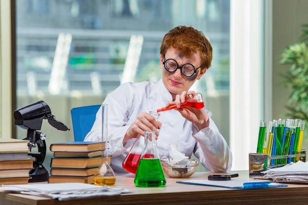 Jeune chimiste fou travaillant dans le laboratoire