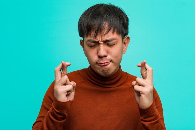 Jeune chinois croisant les doigts pour avoir de la chance