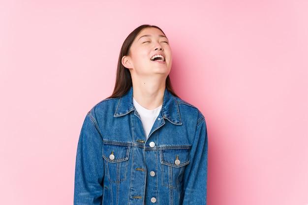 Jeune, Chinois, Femme, Poser, Rose, Mur, Isolé, Détendu, Heureux, Rire, Cou, Tendu, Projection, Dents Photo Premium