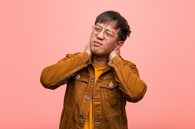 Jeune chinois vêtu d'une veste souffrant de douleurs au cou