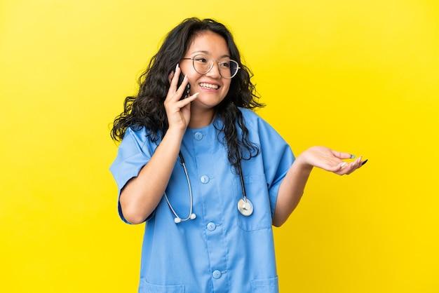 Jeune chirurgien médecin femme asiatique isolée sur fond jaune gardant une conversation avec le téléphone portable avec quelqu'un