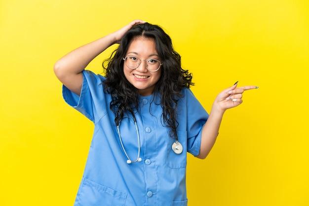 Jeune chirurgien médecin femme asiatique isolée sur fond jaune surpris et pointant le doigt sur le côté