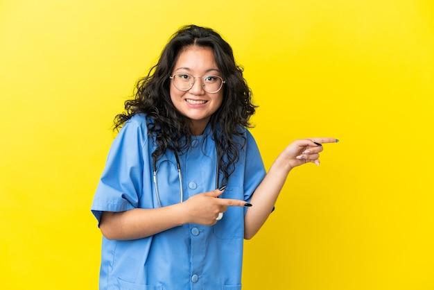 Jeune chirurgien médecin femme asiatique isolée sur fond jaune surpris et pointant vers le côté