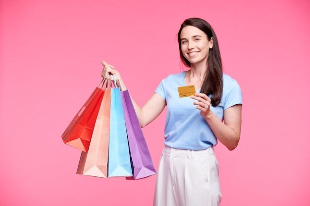 Jeune client joyeux avec plusieurs sacs en papier montrant une carte en plastique qu'elle utilisait pour payer les marchandises