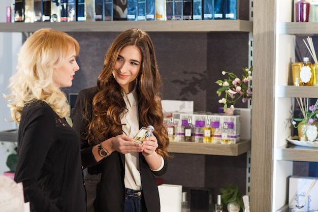Jeune client souriant au service d'une vendeuse positive dans une parfumerie.