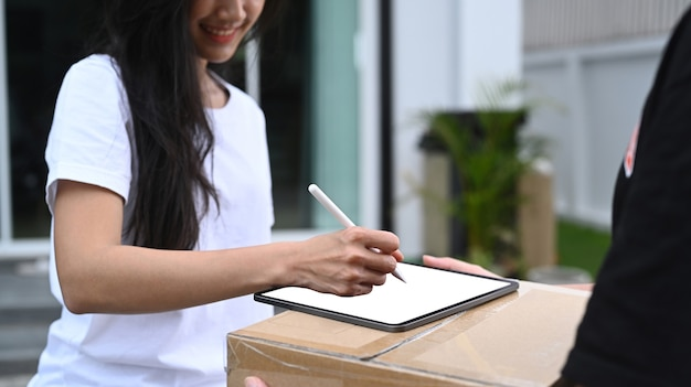 Jeune cliente asiatique signant sur une tablette numérique et recevant le colis du livreur à la maison.