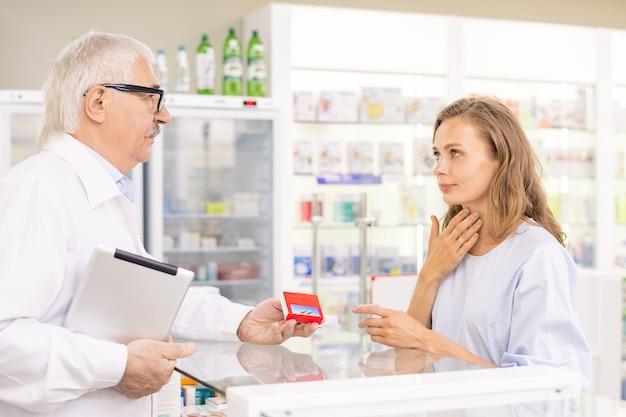 Jeune cliente blonde touchant son mal de gorge tout en demandant à un cadre supérieur de la pharmacie de lui donner quelque chose pour réduire la douleur