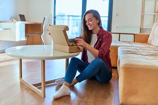 Une jeune cliente joyeuse et souriante a reçu un colis et déballé une boîte en carton avec une commande en ligne, un bon service de livraison