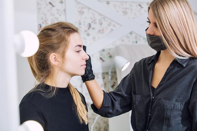 Une jeune cliente peint et prépare les sourcils d'un maître professionnel dans un salon de beauté